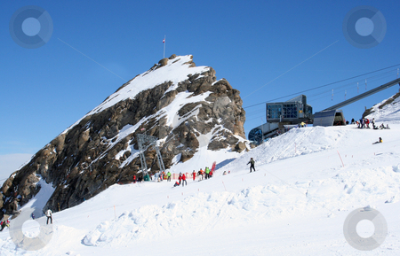 Skiers and lift on Alps mountains stock photo, Skiers on Alps mountains with ski lift in background, Austria. by Martin Crowdy
