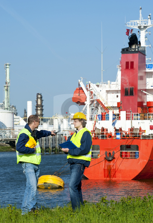 Dockers stock photo, Dockers discussing an issue with a moored ship in an industrial harbor by Corepics VOF