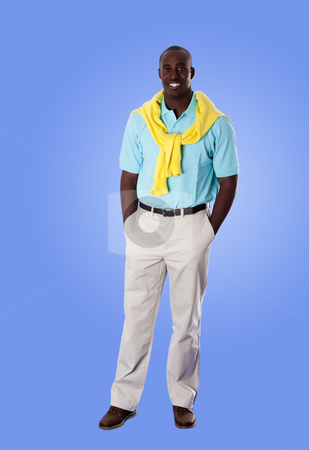Happy African American business man stock photo, Handsome happy African American corporate business man smiling, standing with hands in pocket, wearing blue shirt and yellow sweater around his neck and khakis, isolated. by Paul Hakimata