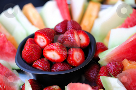 Strawberry And Melon Slices stock photo, A bowl of cleaned strawberries surrounded by slices of watermelon cantaloupe and honeydew melon by Lynn Bendickson