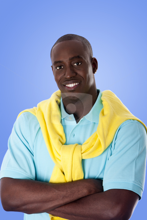Happy African American business man stock photo, Handsome happy African American corporate business man with arms crossed, wearing blue shirt and yellow sweater around his neck, isolated. by Paul Hakimata