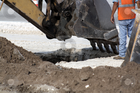 Excavator Bucket Digging a Hole stock photo, The bucket of an excavator is poised to dig further into a hole at the feet of a worker on a roadway project. by Carl Stewart