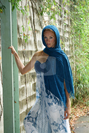 Beautiful Redhead with Blue Head Scarf stock photo, A lovely young redhead wearing a blue pattern dress and a matching head scarf stands next to a brick wall with vines. by Carl Stewart