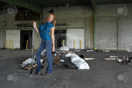 Beautiful Redhead with a Shovel (2) stock photo, A lovely young redhead with a shovel in front of a pile of garbage at a long-abandoned warehouse facility. by Carl Stewart
