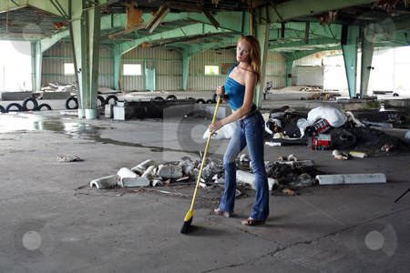 Beautiful Redhead with a Broom (2) stock photo, A lovely young redhead with a broom in front of a pile of garbage at a long-abandoned warehouse facility. by Carl Stewart