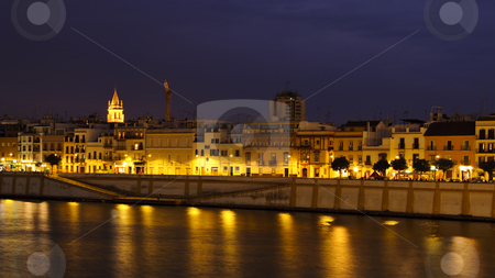 Seville by night stock photo, Night view of the buildings reflecting in the waters of Guadalquivir river in Triana district, Seville, Spain. Photo taken on the 26th of September, 2009. by Alessandro Rizzolli