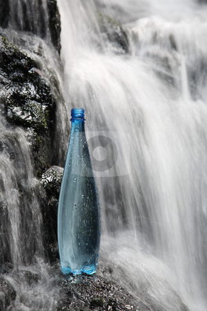 Mineral water in waterfalls stock photo, A blue bottle of fresh mineral water in waterfalls by Laurent Renault
