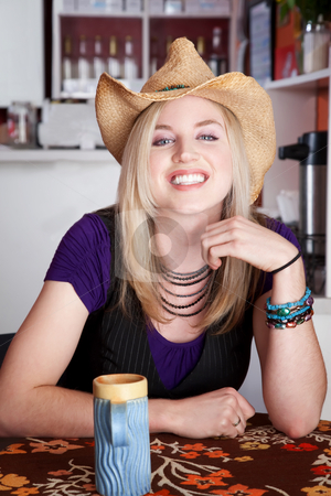 Smiling blonde woman stock photo, Smiling blonde woman with cowboy hat in a cafe by Scott Griessel