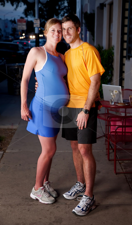 New parents stock photo, Pregnant woman and partner in fitness clothing posing on the sidewalk by Scott Griessel