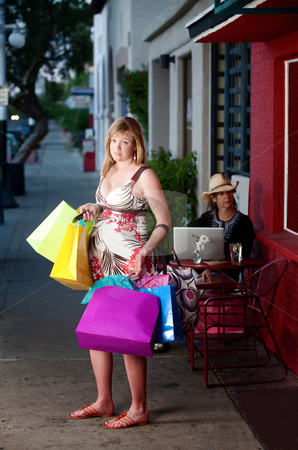 Overwhelmed pregnant woman  stock photo, Overwhelmed pregnant woman holding shopping bags outside on sidewalk by Scott Griessel