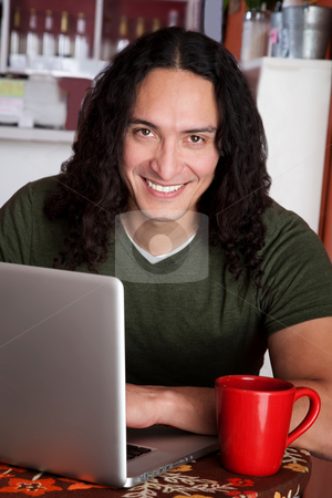 Handsome Native American man stock photo, Handsome Native American man with laptop and red mug by Scott Griessel