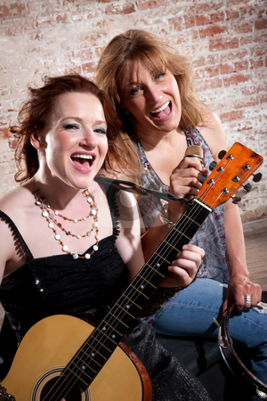 Female musicians stock photo, Female musicians sing along with guitar in front of a brick background by Scott Griessel