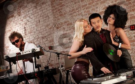 Pretty ladies surrounding a DJ  stock photo, Pretty ladies surrounding a DJ at a 1970s Disco Music Party by Scott Griessel
