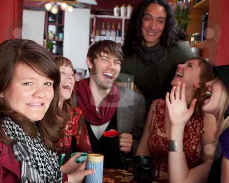 Embarassed woman stock photo, Embarassed woman at a table with laughing friends by Scott Griessel