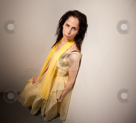 Serious looking woman in a yellow dress stock photo, High angle view of a woman in a yellow dress.  She has a serious expression on her face. by Scott Griessel