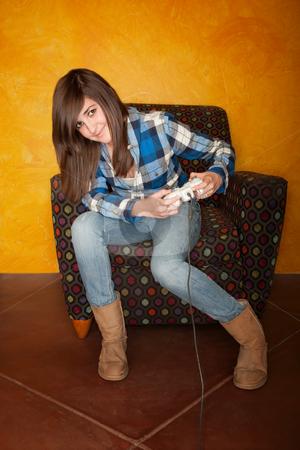 Cute Girl Playing Video Game stock photo, Cute young girl playing a video game by Scott Griessel