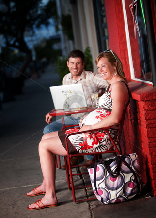 Happy couple sitting outside stock photo, Happy couple sitting outside a cafe with laptop computer by Scott Griessel