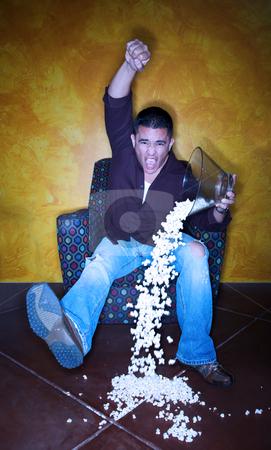 Hispanic sports fan with popcorn watching television stock photo, Male Hispanic sports fan with popcorn watching television by Scott Griessel