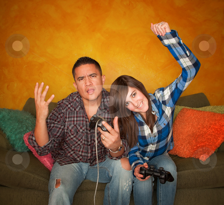 Hispanic Man and Girl Playing Video game stock photo, Attractive Hispanic Man and Girl Playing a Video Game with Handheld Controllers by Scott Griessel