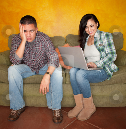 Hispanic Couple with Computer stock photo, Hispanic Couple on Green Couch with Computer Man is Bored by Scott Griessel