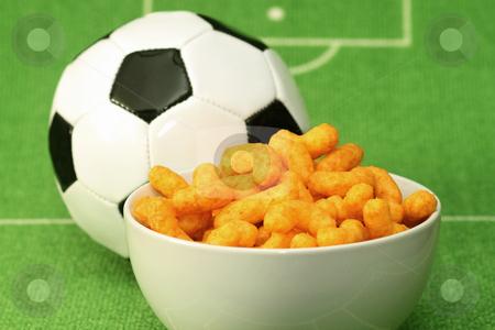 Crispy Snacks stock photo, Soccer ball with crispy snacks in a bowl on green background by Birgit Reitz-Hofmann