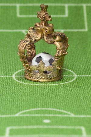 Soccer trophy stock photo, Symbol photo - crown on a soccer field. Shot in studio. by Birgit Reitz-Hofmann