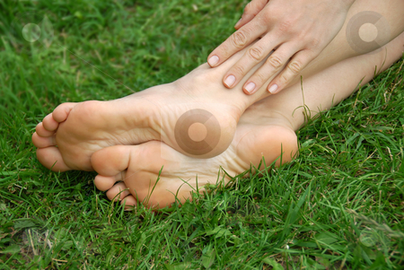 Woman feet stock photo, Woman healthy feet and hand over green grass outdoor by Julija Sapic