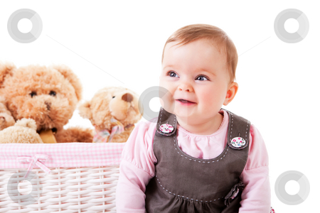 Toddler Sitting Next to Teddy Bears stock photo, A baby girl is sitting next to a basket of teddy bears and smiling.  Horizontal shot. by Angela Hawkey