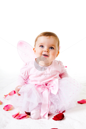 Toddler in a Fairy Outfit stock photo, A cute baby girl dressed in a fairy costume sits amongst flower petals and smiles upwards.  Vertical shot. by Angela Hawkey