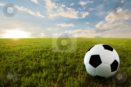 Soccer ball in meadow stock photo, Soccer ball on meadow in sunset time by Giordano Aita