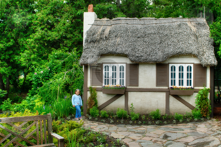 Child House stock photo, A little girl standing next to a small thatch roofed house by Richard Nelson