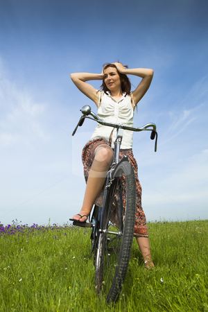 Girl with a bicycle stock photo, Happy young woman on a green meadow with a vintage bicycle by ikostudio