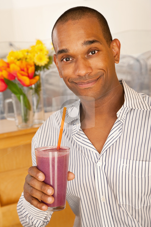 Man Holding a Smoothie stock photo, Man is holding a smoothie while smiling at the camera.  Vertical shot. by Scott Griessel