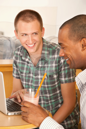 Two Men at Cafe Using Laptop stock photo, Young men at a cafe using a laptop computer. Vertical shot. by Scott Griessel