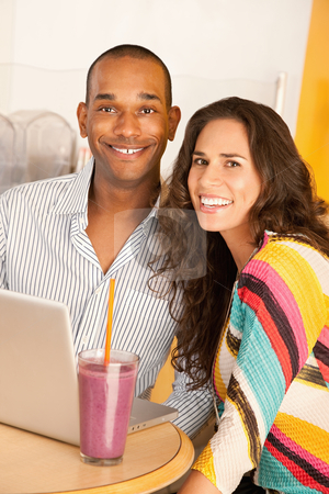 Couple With a Laptop stock photo, Young couple smile towards the camera while seated at a laptop and smoothie.  Vertical shot. by Scott Griessel