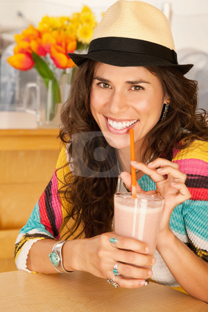 Woman Drinking a Smoothie stock photo, A woman is drinking a beverage from a cup and smiling at the camera.  Vertical shot. by Scott Griessel