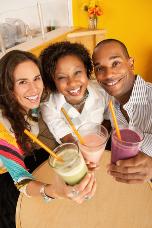Three People Dining Out stock photo, High angle view of three people at a cafe drinking frozen beverages. Vertical shot. by Scott Griessel