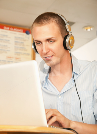Young Man with Laptop and Headphones stock photo, A young man using a laptop and listening to headphones. Vertical shot. by Scott Griessel