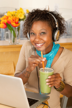 Woman With Laptop and Smoothie stock photo, Woman works on her laptop while holding a smoothing and smiling at the camera.  Vertical shot by Scott Griessel