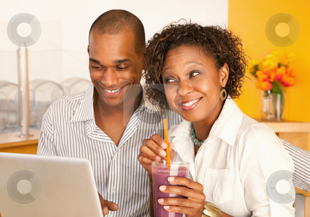 Couple on a Laptop stock photo, Young couple smile as they work on a laptop.  The woman is holding a smoothie.  Horizontal shot. by Scott Griessel
