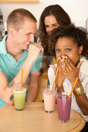 Three People Dining Out stock photo, Three people at a cafe drinking frozen beverages. Vertical shot. by Scott Griessel