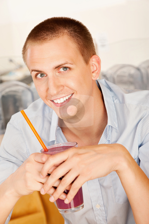 Young Man Drinking a Smoothie stock photo, A young man holding a frozen beverage. Vertical shot. by Scott Griessel