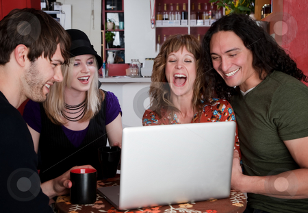 Four friends in a coffee house stock photo, Four friends in a coffee house with laptop computer by Scott Griessel