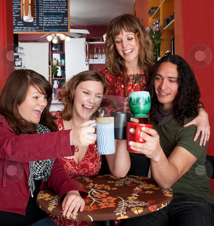 Four young friends toasting at a cafe stock photo, Four young friends toasting at a cafe by Scott Griessel