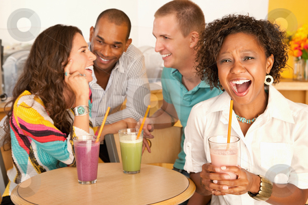 Group of Friends Talking stock photo, A group of young friends are socializing over smoothies.  One woman is smiling at the camera.  Horizontal shot. by Scott Griessel