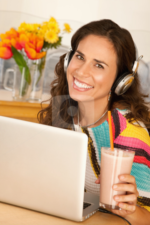 Woman Drinking a Smoothie stock photo, A woman is seated at a desk with a laptop and is drinking a beverage from a cup.  She is wearing headphones and smiling at the camera.  Vertical shot. by Scott Griessel