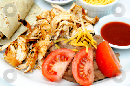 Grilled Shredded Chicken stock photo, Grilled chicken shredded ready to make tacos with refried beans sliced tomato tortillas and small bowls of hot sauce cheese and onion by Lynn Bendickson