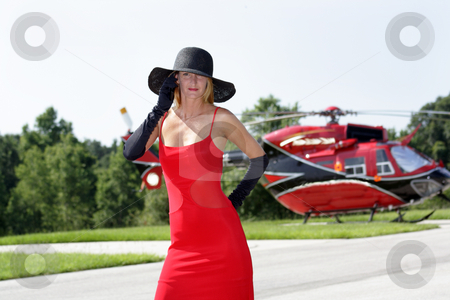Woman in Front of a Helicopter (1) stock photo, A beautiful blonde dressed in a long red gown with long black gloves and a black hat stands in front of a matching red and black helicopter. by Carl Stewart
