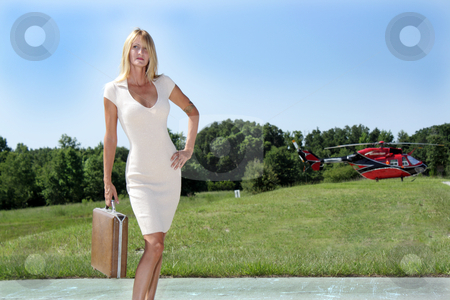 Businesswoman in Front of a Helicopter (1) stock photo, A beautiful blonde businesswoman holding a briefcase and wearing a cream-colored dress, stands in front of a red and black helicopter. by Carl Stewart