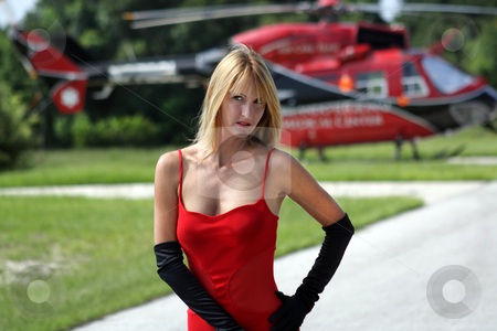 Woman in Front of a Helicopter (9) stock photo, A beautiful blonde dressed in a long red gown with long black gloves stands in front of a matching red and black helicopter. by Carl Stewart